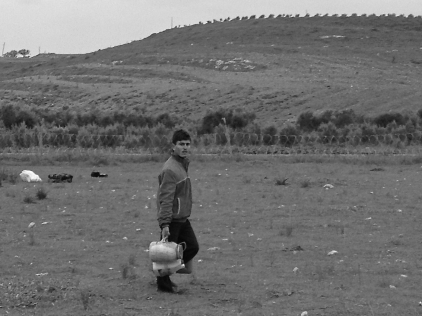 A young man carries food as he prepares to cross the border fence and embark on a journey with no known end