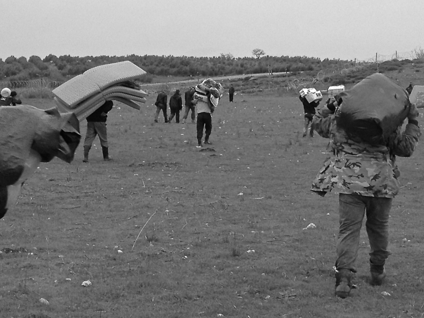 Syrians, displaced from the violence that has gripped the country, carry their essential belongings across a grassy field towards the barbed wire border fence that separates their country from Turkey